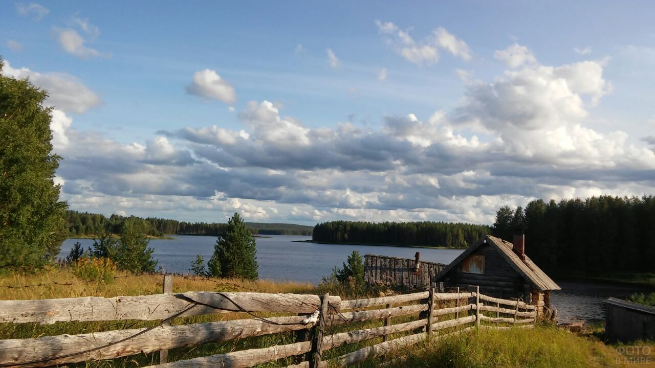 Белые облака плывут над деревней и лесным озером