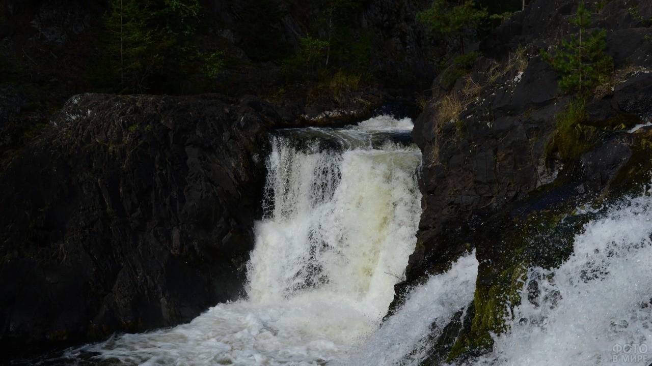 Бурный водопад падает с каменистых гор