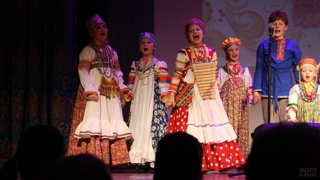 Дети в народных костюмах поют на сцене для своих мам