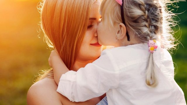 Девочка целует в нос красавицу-маму