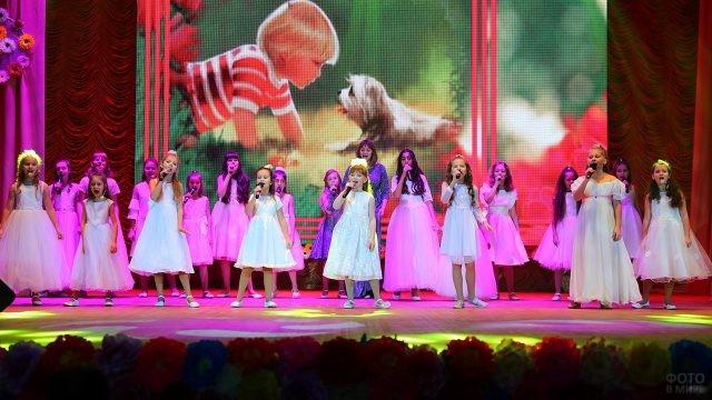 Девочки в нарядных платьях поют на сцене