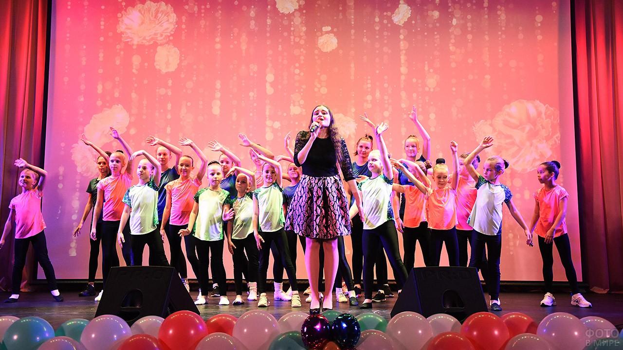 Маленькие артисты на сцене выступают на праздничном концерте