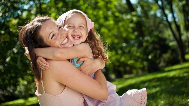 Мама обнимает дочку в зелёном парке