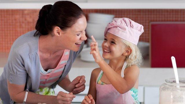 Мама с дочкой дурачатся во время готовки