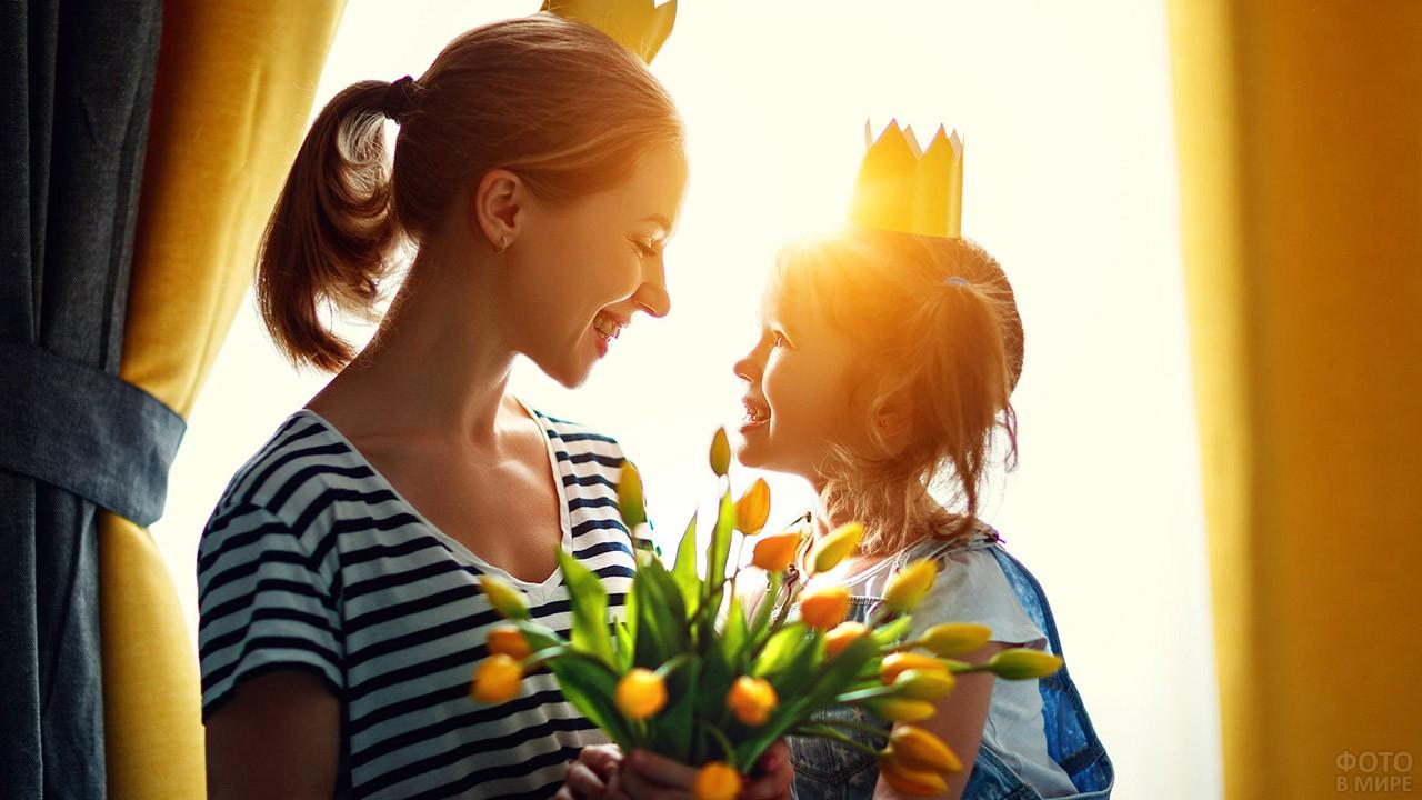 Мама с дочкой в коронах на фоне солнечного света в окне