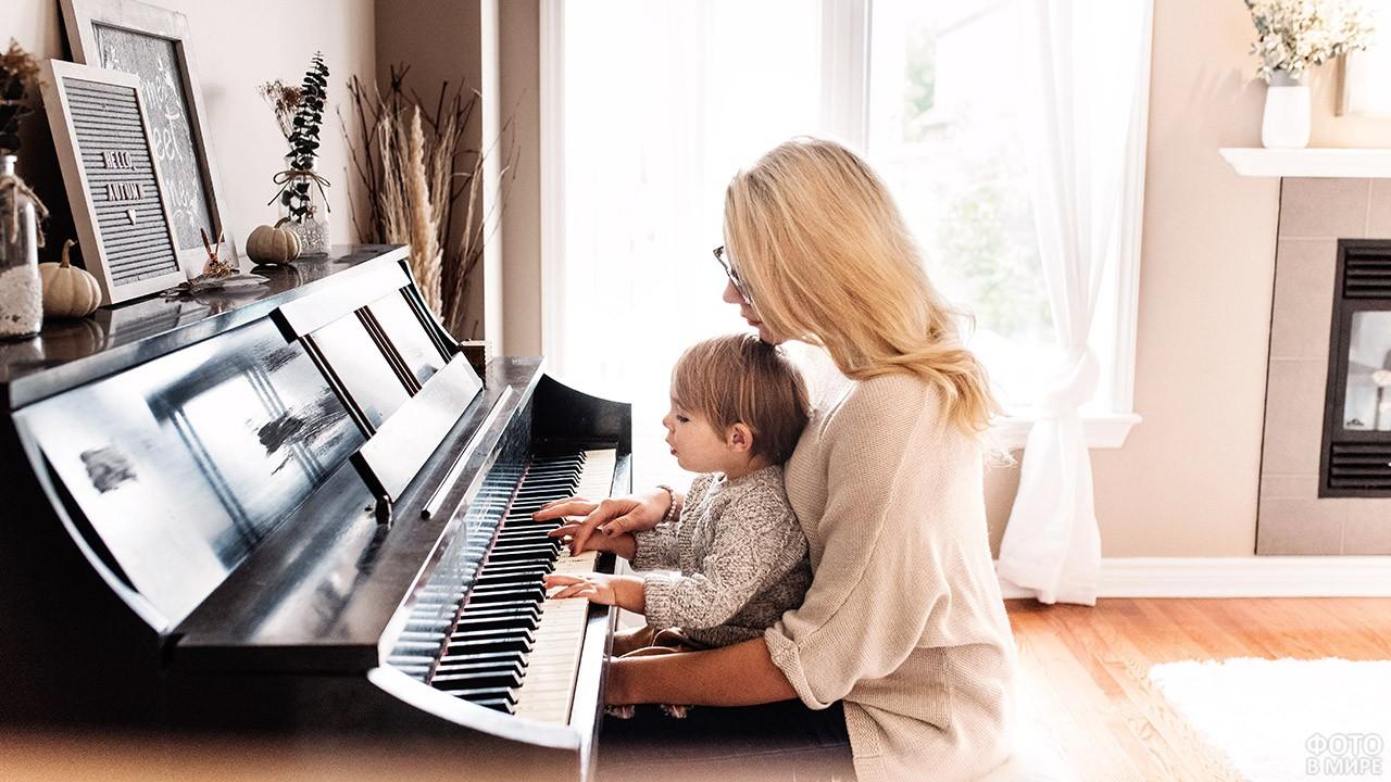 Мама с малышом на коленях сидит за фортепиано