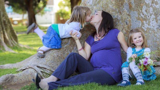 Многодетная мама сидит под деревом с дочерьми