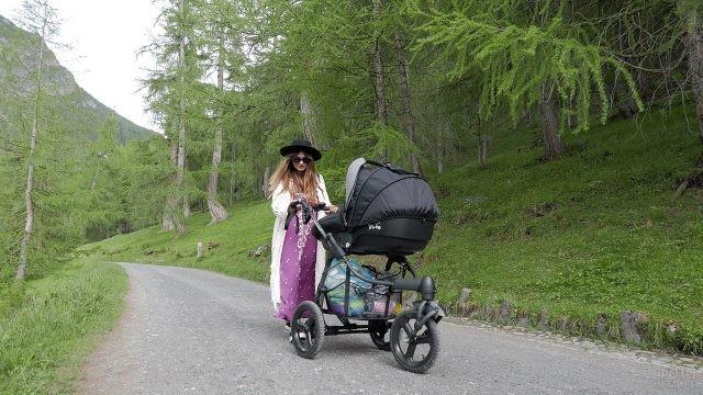 Молодая мама с коляской в парке