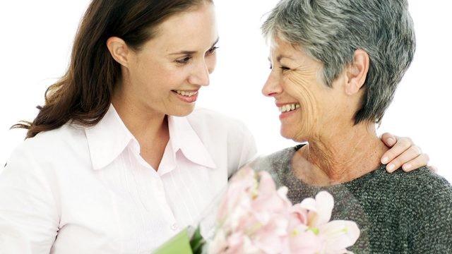 Молодая женщина дарит букет своей маме