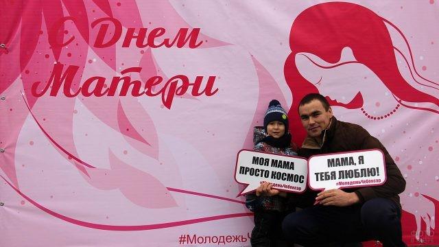 Отец с сыном в праздничной фотозоне с поздравлениями для мамы