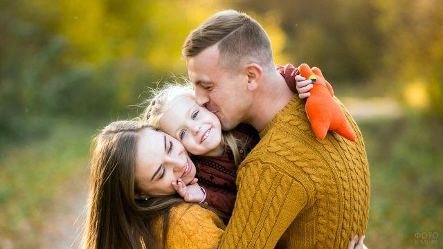 Папа, мама и дочка обнимают друг друга в осеннем парке