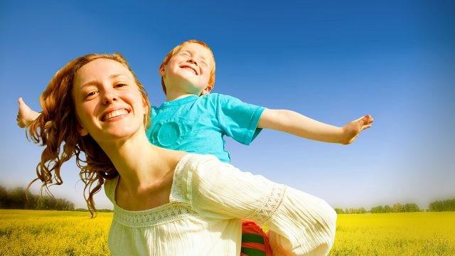 Улыбающаяся мама с рыжеволосым сыном в летнем поле