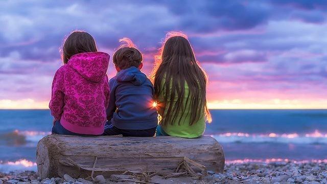 Дети сидят втроём на вечернем пляже
