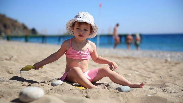 Девочка в панамке сидит на пляже