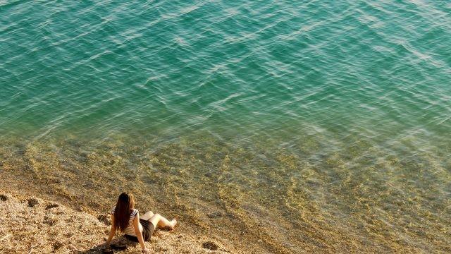Девушка сидит у кромки воды