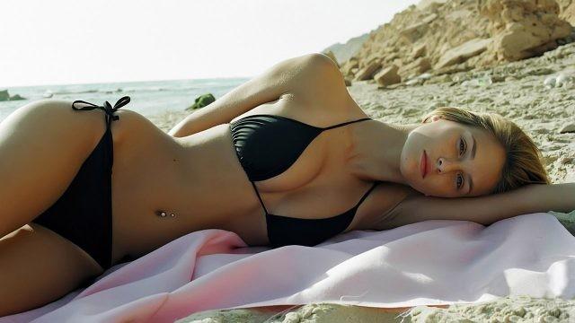 Девушка в чёрном бикини лежит на диком пляже