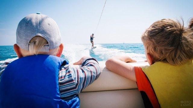 Мальчишки смотрят с катера на кайт-сёрфера