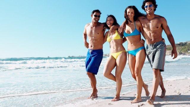 Молодые парочки идут по мелководью пляжа