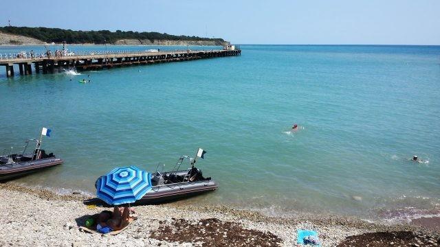 Отдыхающие под зонтиком на пляже Института океанологии