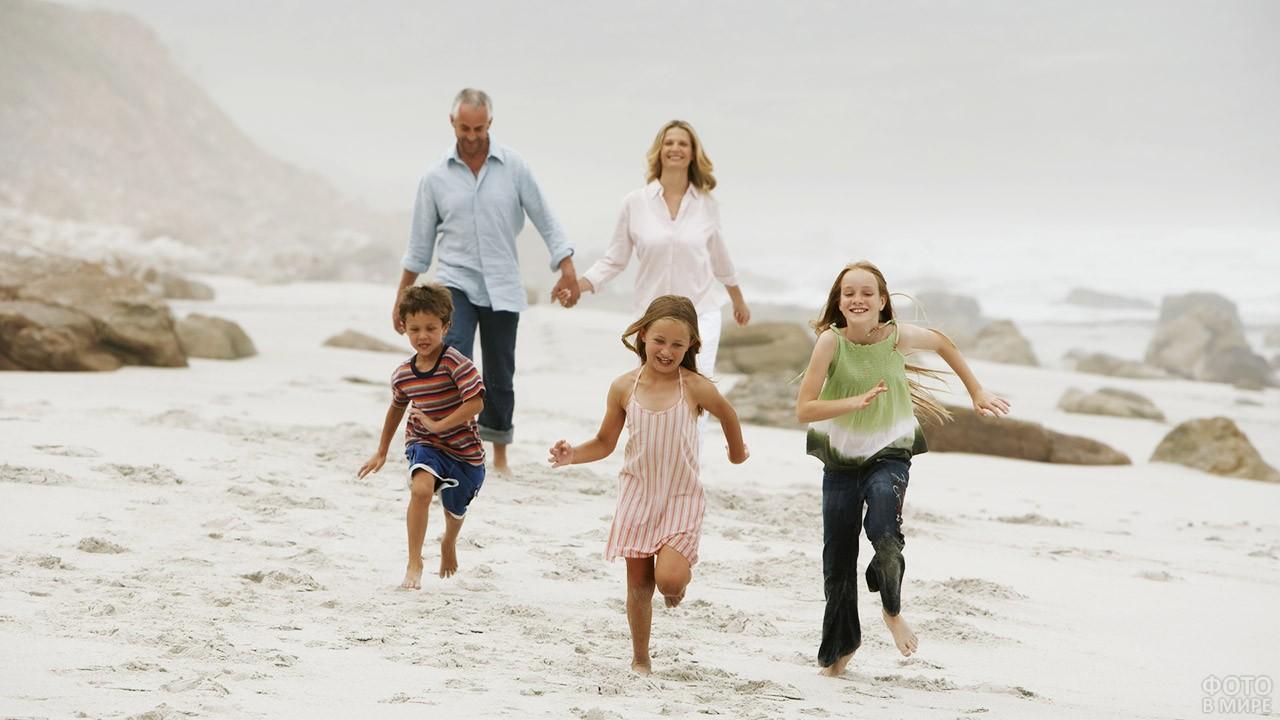 Пара с детьми гуляют по дикому пляжу