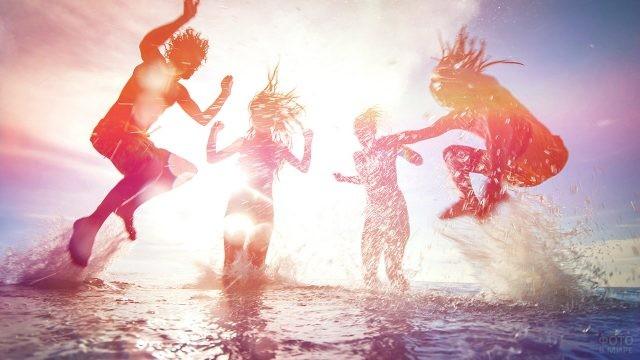 Силуэты резвящихся в воде молодых людей на фоне солнца