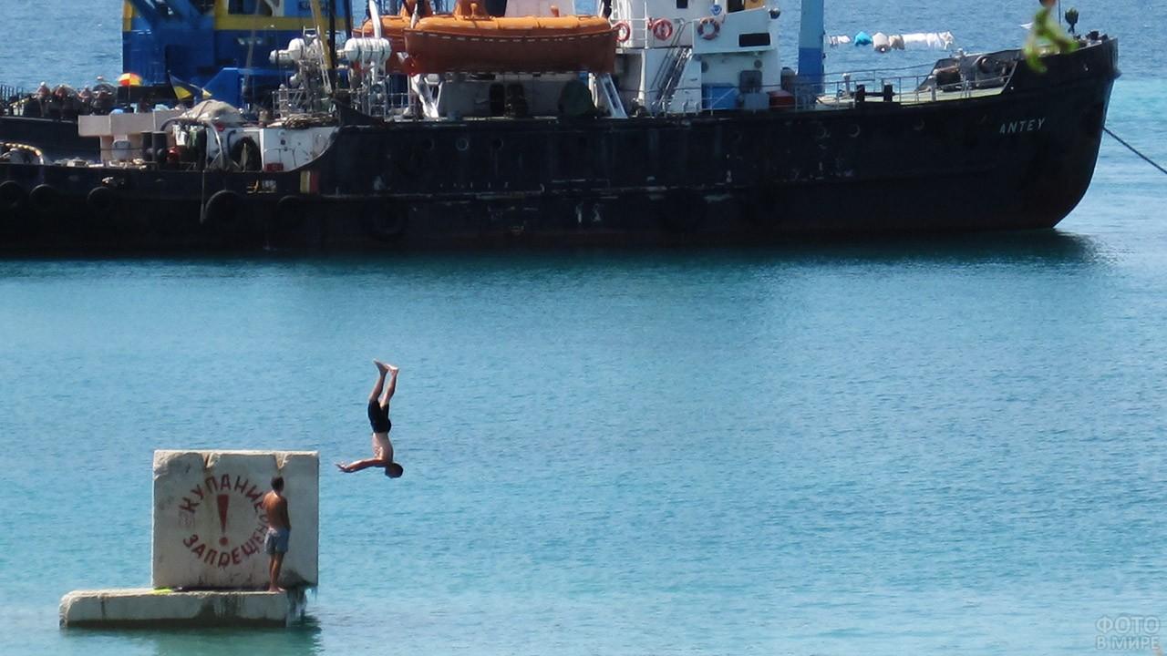 Туристы ныряют с указателя Купание запрещено