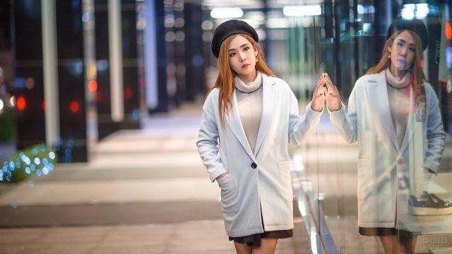Азиатка в берете заглядывается на витрины магазинов