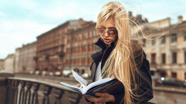 Блондинка читает книгу на набережной