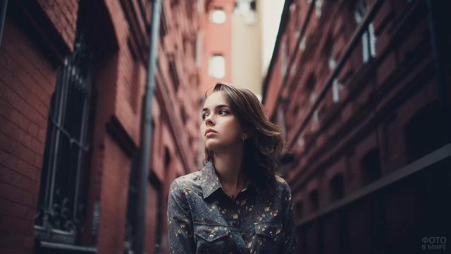 Девушка между кирпичных домов