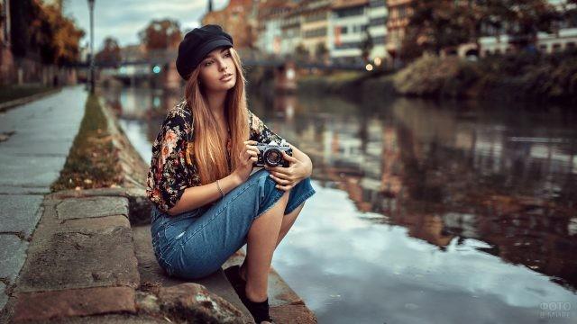 Девушка с фотоаппаратом на берегу реки