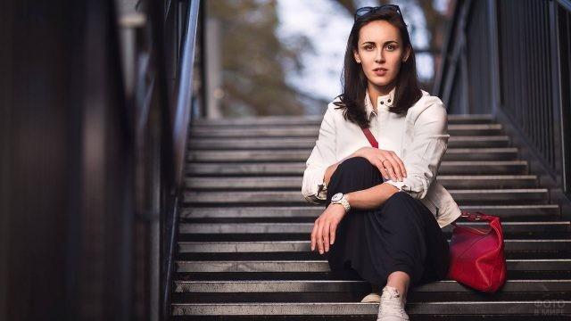 Девушка с красной сумочкой сидит на лестнице