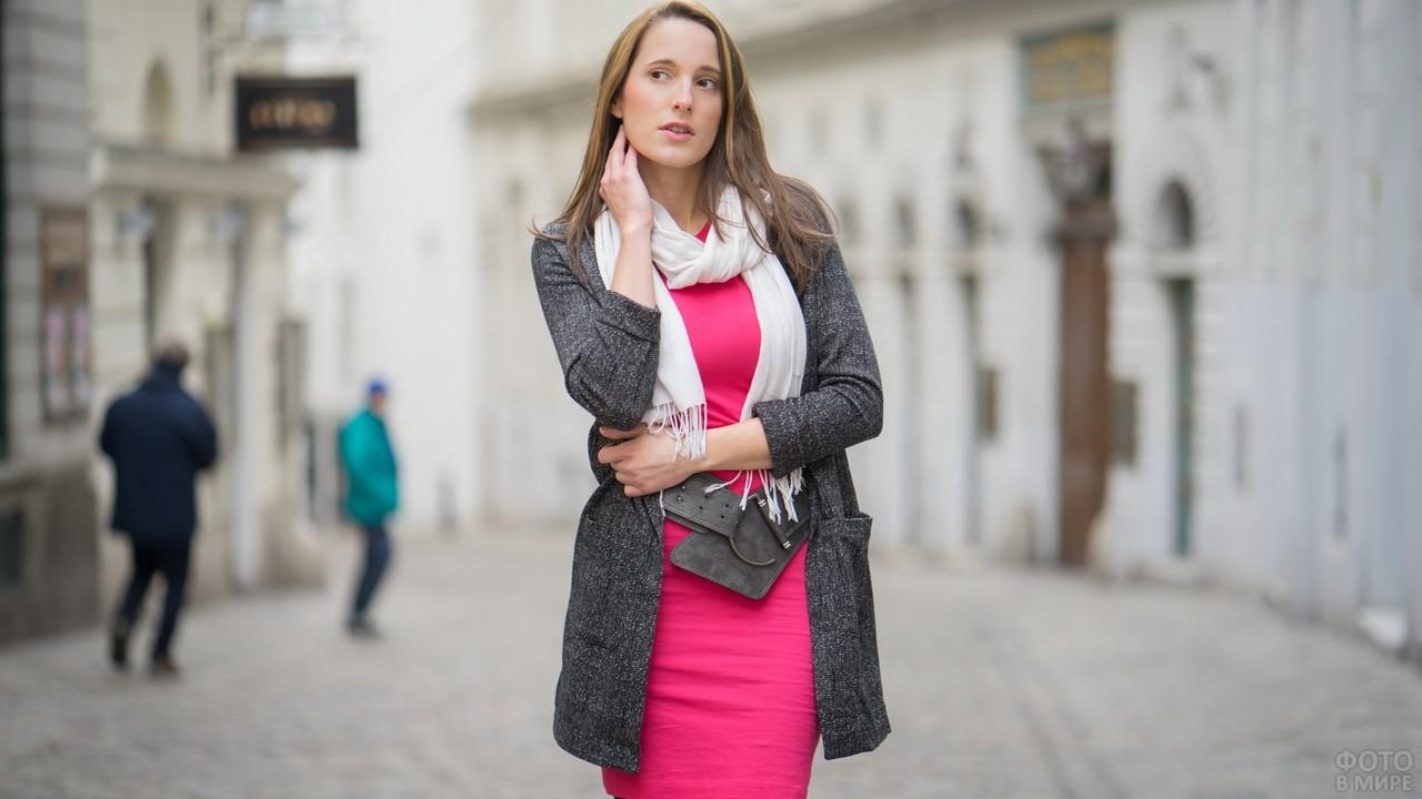 Девушка в розовом платье задумалась на улице
