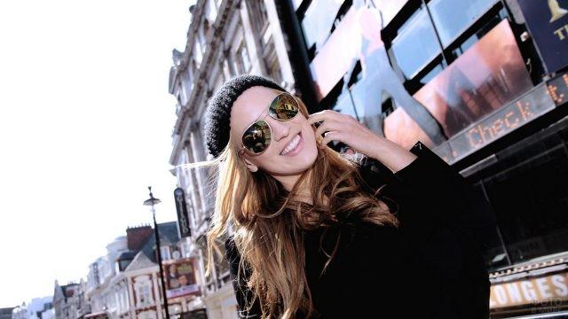 Девушка в солнцезащитных очках и шапке на фоне офисов