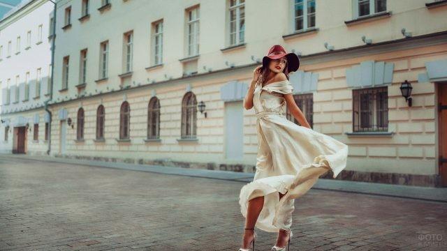 Девушка в воздушном платье прогуливается по городу