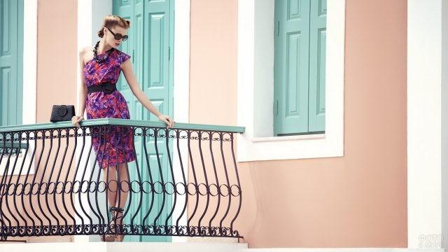 Красивая девушка на балконе розового дома