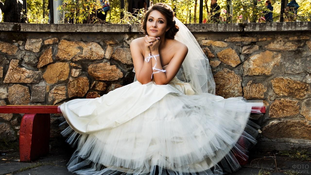 Невеста на лавочке возле каменной стены