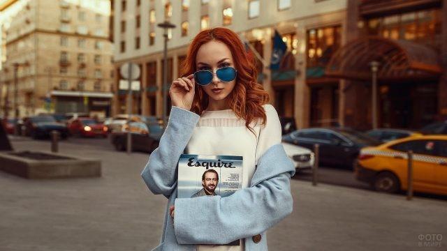 Рыжая девушка в синих очках с журналом Эсквайр