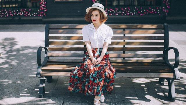 Скромная девушка в шляпе сидит на лавочке