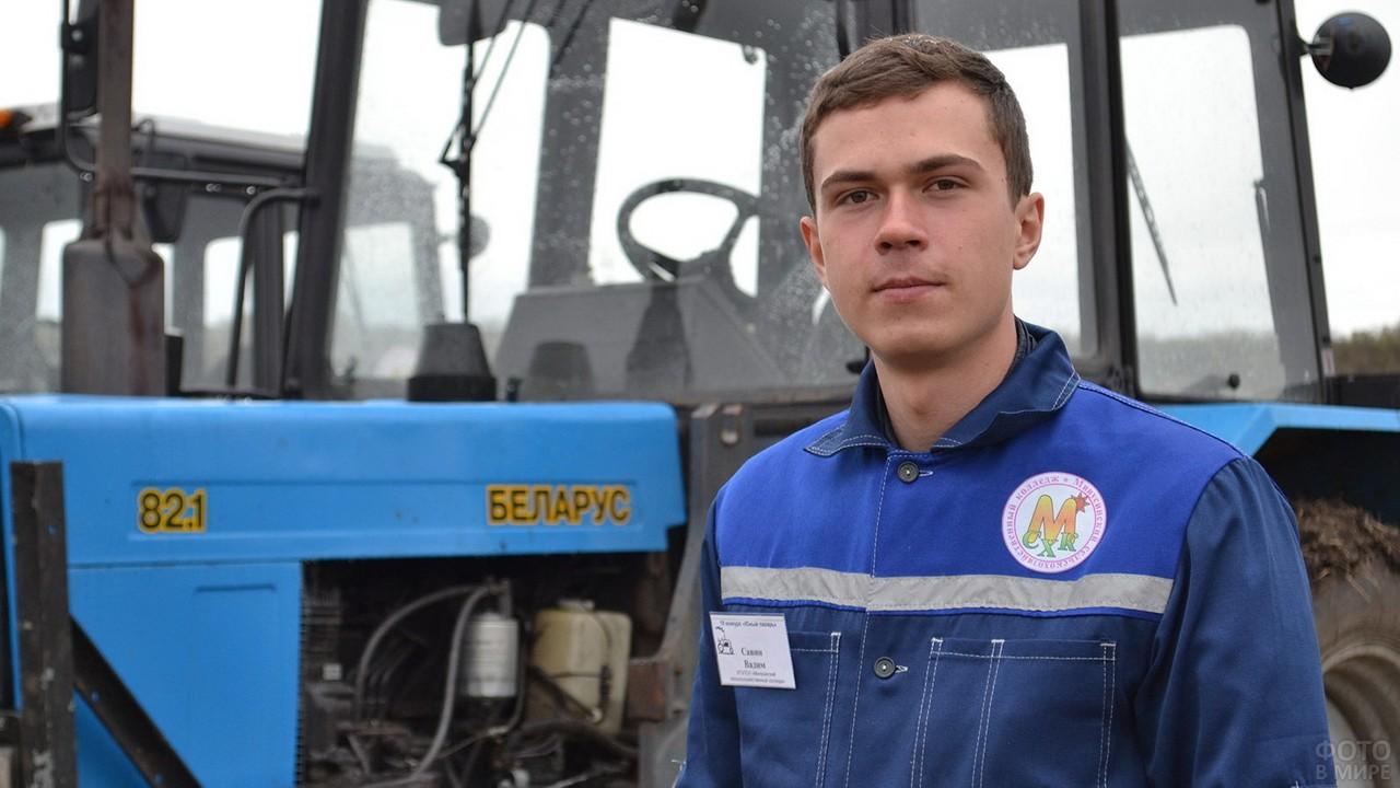 Молодой тракторист на фоне техники
