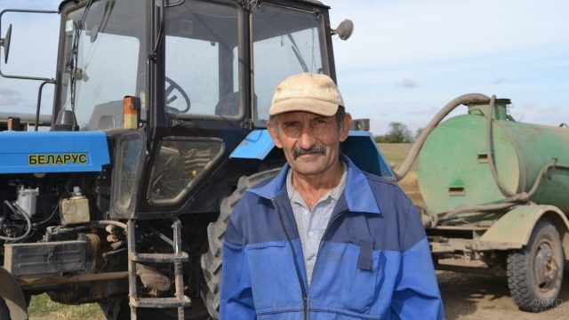 Мужчина на фоне трактора с бочкой-прицепом