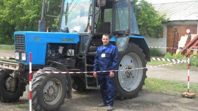 Мужчина возле трактора за ограждением