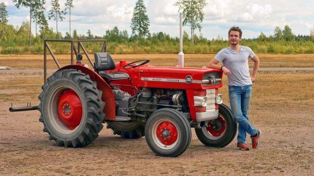 Парень облокотился на красный трактор