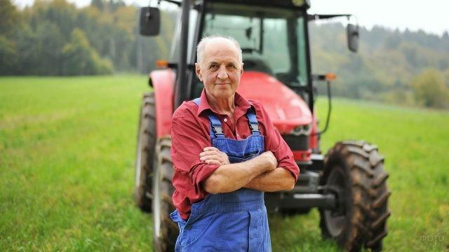 Пожилой мужчина стоит перед трактором