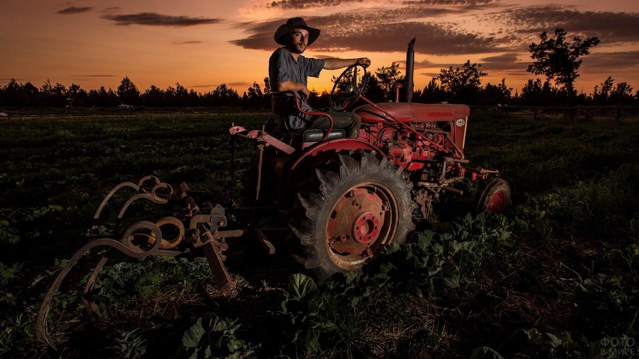 Тракторист на красном тракторе вечером