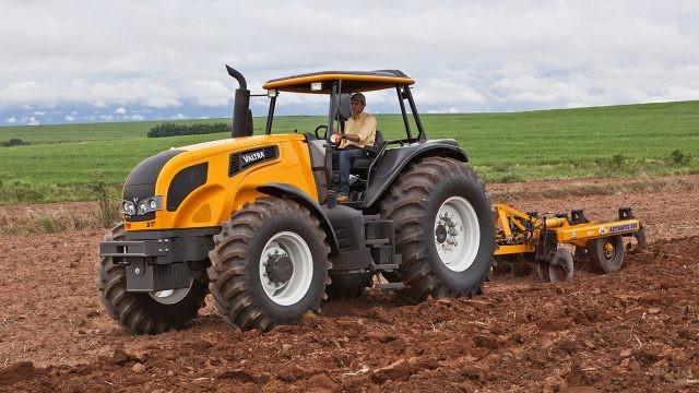 Тракторист на тракторе Valtra пашет землю