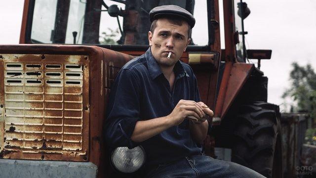 Тракторист в кепке облокотился на фару