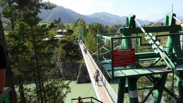 Люди идут по подвесному мосту