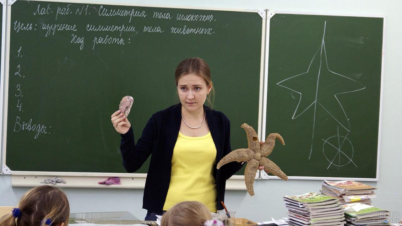 Молодая учительница биологии у доски с задачей