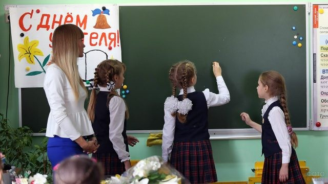 Школьницы пишут на доске с плакатом к Дню учителя