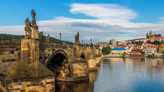 Каменные арки и старинные статуи на панораме Праги
